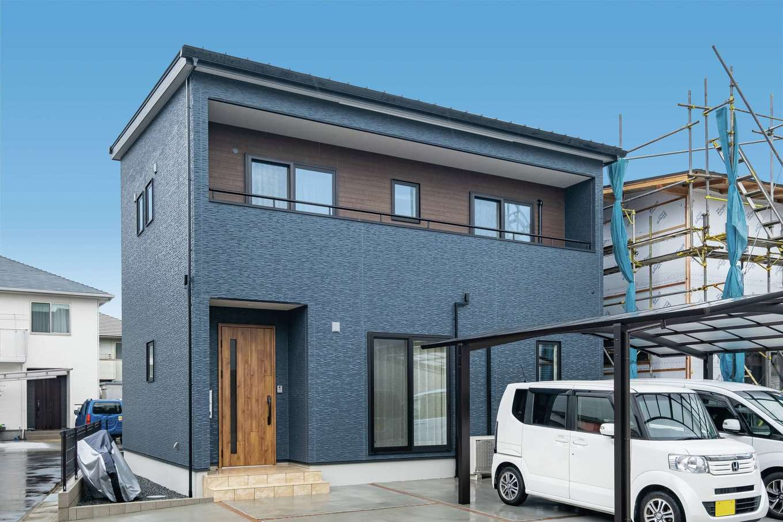 イデキョウホーム【デザイン住宅、収納力、省エネ】ツートンカラーが希望だったという外観は、ネイビーに木目調をプラス。3方が道路に面しているため、各方向からのデザインにも配慮しながら設計されている