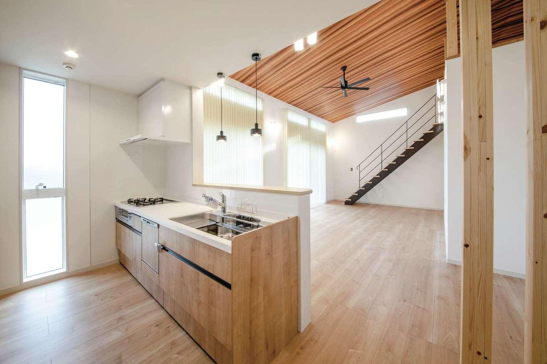 未来創建【デザイン住宅、省エネ、平屋】板張りの天井が目を惹くリビングダイニング。天井高が一番高いところで3.8メートルもあり開放感抜群だ。「将来、家族が増えたとき、子どもがピアノを弾く様子を見ながら料理をしたい」と考え、キッチンの横にピアノを置くための凹みをつくったそう