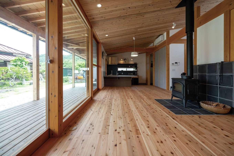 建杜 KENT(大栄工業)【自然素材、建築家、平屋】杉の床と勾配天井が清々しいリビング。ウッドデッキには深い軒を張り出した。大きな木製サッシは造作