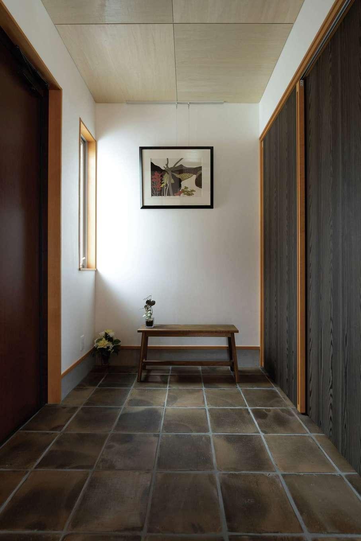 建杜 KENT(大栄工業)【自然素材、建築家、平屋】小さなギャラリーのような玄関ホールにはテラコッタタイルを用いた。シューズクローゼットの扉は、Nさんが貼った焼き杉を模したクロス