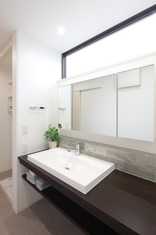 トキノハウス(常盤工業)【浜松市東区半田山3丁目41-1・モデルハウス】ホテルライクを感じさせるスタイリッシュな洗面。奥の洗濯機置き場の上には、タオルや洗剤置き場としても活用できる可動棚を設置。日常でよく使う場所だからこそ、使いやすく、そして、お気に入りの空間に