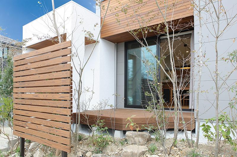 トキノハウス(常盤工業)【浜松市東区半田山3丁目41-1・モデルハウス】ほどよくグリーンに囲まれる住まい。こもれ日がさしこむウッドデッキでくつろぎタイム。植栽と木ルーバーでやわらかく仕切り、プライベートなスペースを確保