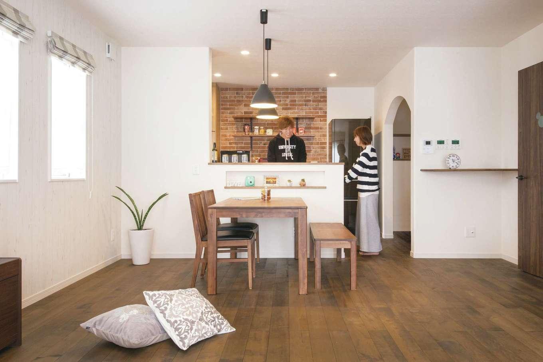 ユニバーサルホーム(浜松東店・掛川店)【デザイン住宅、自然素材、間取り】夫妻の好みを詰め込んだ、無垢の木と白壁のコントラストが居心地いいLDK。木製キッチンやレンガ調タイル、アイアン調の照明もよく映える。「私たちも意見を言いましたが、コーディネーターさんがうまくまとめてくださいました」とおふたり