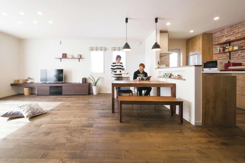 ユニバーサルホーム(浜松東店・掛川店)【デザイン住宅、自然素材、間取り】無垢材の床にレンガ調タイル、デザイン照明が映えるLDK。ここでくつろぐのが夫婦の楽しみで、ご主人の趣味の筋トレを一緒に行うことも