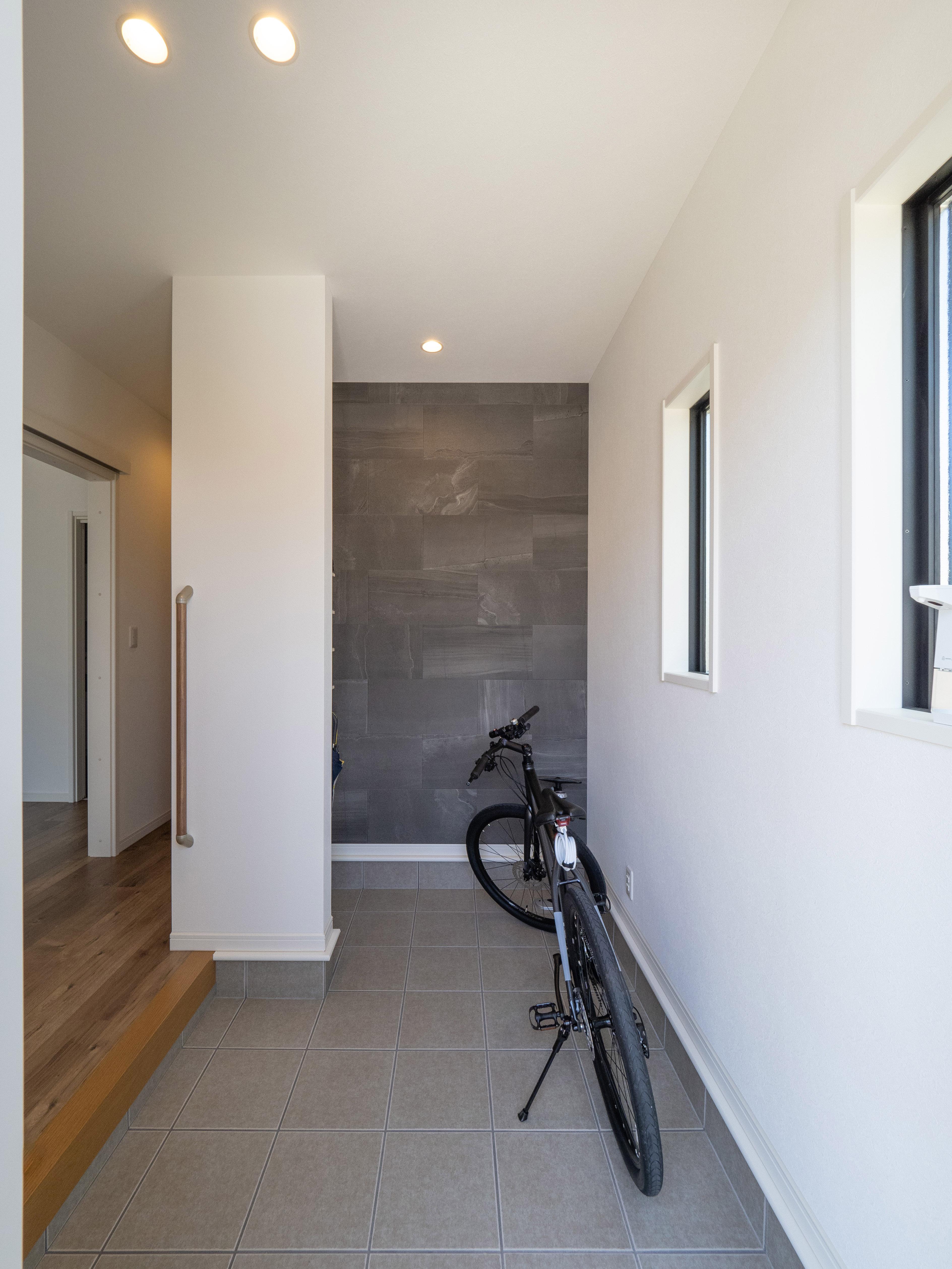 クレバリーホーム浜松東店【デザイン住宅、夫婦で暮らす、間取り】奥行きのある玄関土間。ご主人のマウンテンバイクを置いても十分なスペースを確保。ベビーカーやお子様の自転車も置くことができる。奥の壁には、デザインだけでなく脱臭・調湿効果もあるエコカラット を施工した