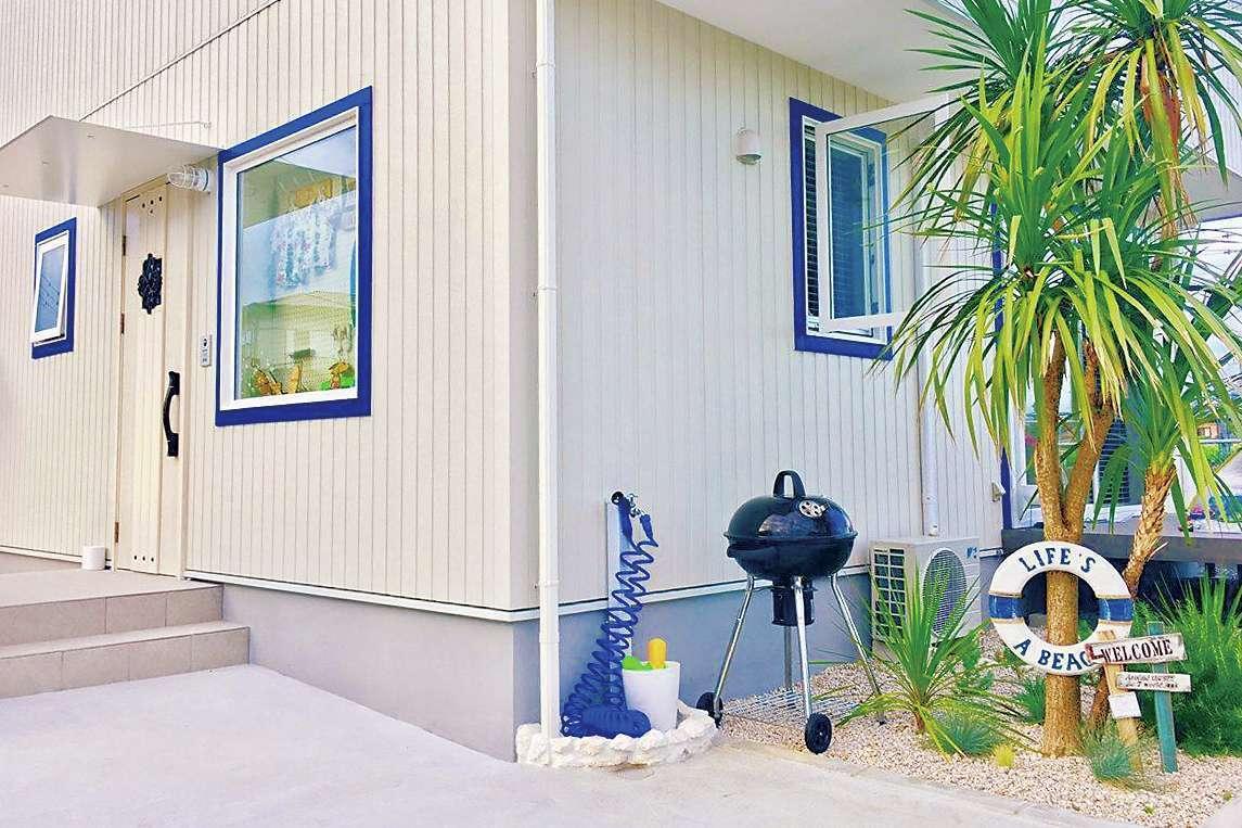Art Wood Home (永建)【デザイン住宅、インテリア、子育て】白い外壁に窓枠のマリンブルーが映え、シーサイドにある家を想像させる。Mさん夫妻が雑貨をコーディネートしたエクステリアが、リゾート感をさらにアップする