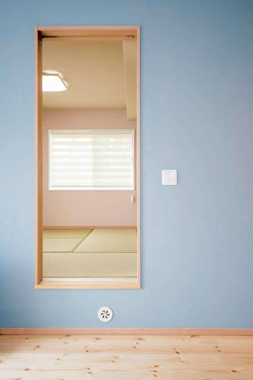Art Wood Home (永建)【省エネ、収納力、インテリア】ブルーの壁の引き戸の向こうは和室。一段高くし、4.5畳の床下すべてを収納スペースに