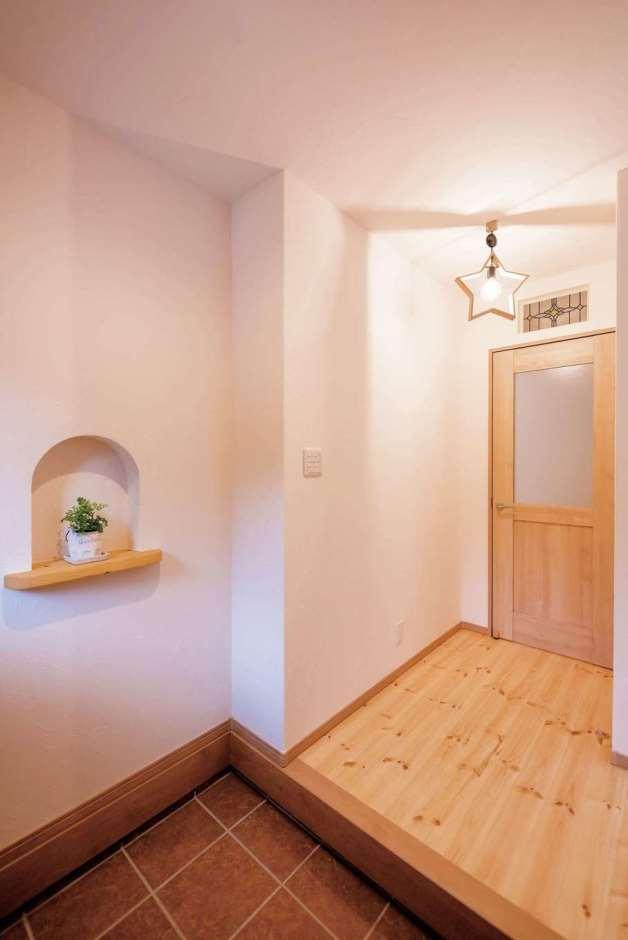 Art Wood Home (永建)【省エネ、収納力、インテリア】ニッチと星型の照明がアクセントの玄関。テラコッタのタイルとパイン材の床の素材感がナチュラルでかわいい