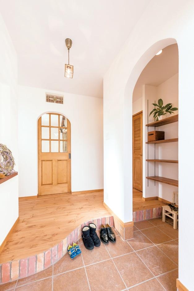 Art Wood Home (永建)【輸入住宅、自然素材、デザイン住宅】ブリックタイルを貼った玄関ホール。リビングへと続くR開口と、その上に配されたステンドグラスがかわいい