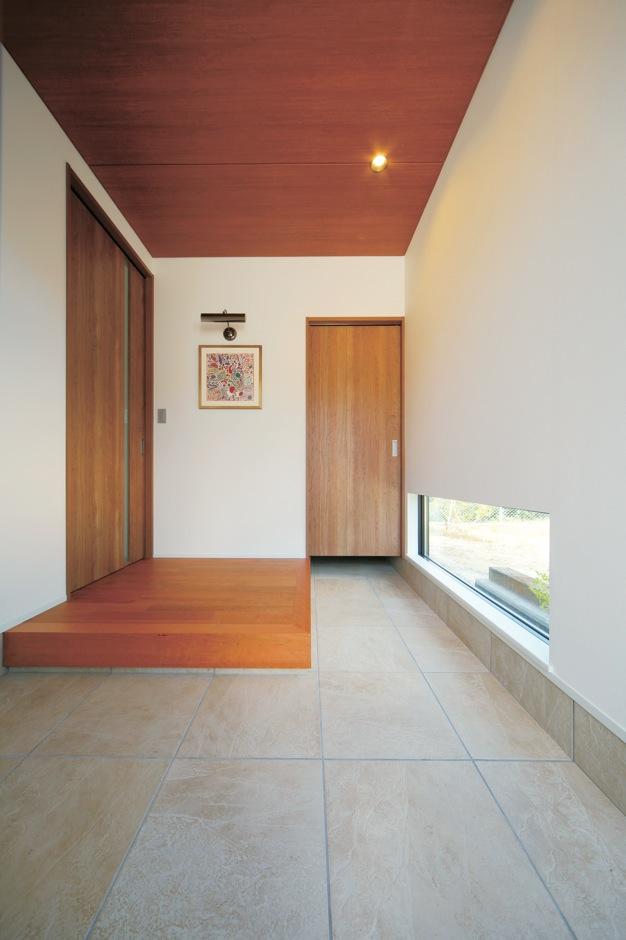 ココハウス【デザイン住宅、収納力、間取り】玄関は大判のタイルを用いた土間と建具や床の木がベストマッチ。土間の奥にシューズクロークも設けてある