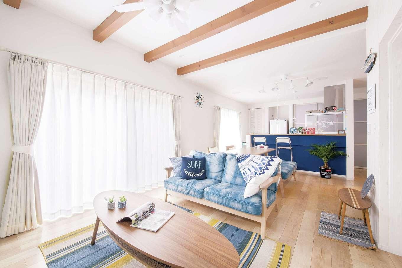"""夫婦の""""好き""""が集まるLDK。白を基調とした空間に青のキッチンが映える。大小のインテリアも西海岸や海をイメージさせるものに統一し、毎日が大好きな""""カリフォルニアスタイルの家""""を実現した"""