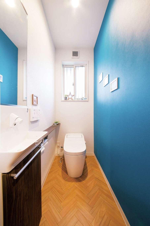 広々としたトイレは青い壁と、ヘリンボーンの床で海を感じる空間に