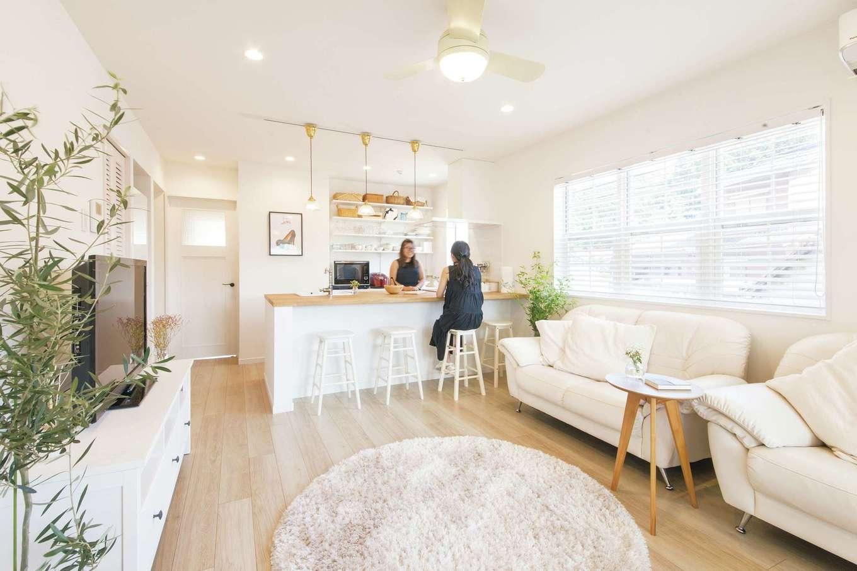 SEVEN HOUSE/セブンハウス【デザイン住宅、二世帯住宅、インテリア】目にも眩しい、真っ白なLDK。オープンな対面キッチンの背面は見せる収納に。ナチュラルな食器やカゴが整然と並ぶ。華やかで温かみのある空間になっている
