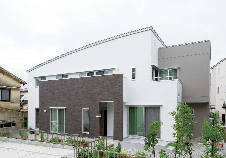 R屋根とキュービックを組み合わせた、形状のコントラストを楽しむ家。白、グレー、茶のモダンな建物に植栽がぬくもりを与える