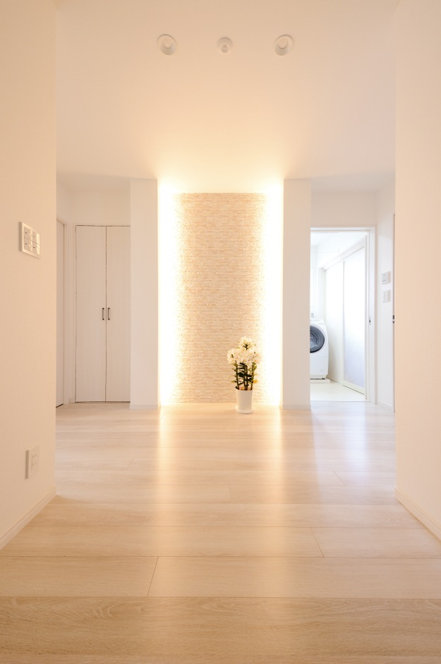 玄関はスペースを広くとり、アクセントウォールと間接照明を効果的に活かして上質で洗練された空間を実現