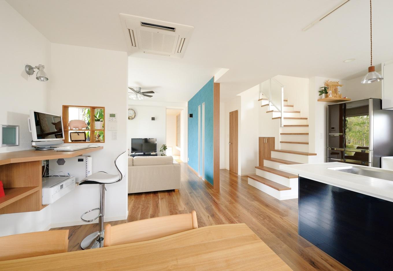 ハウジング小林【デザイン住宅、収納力、間取り】階段の流れるようなラインや、ブルーのアクセントウォールが個性的なLDK。右手に見えるのはダイニングカウンターを兼ねた対面キッチン