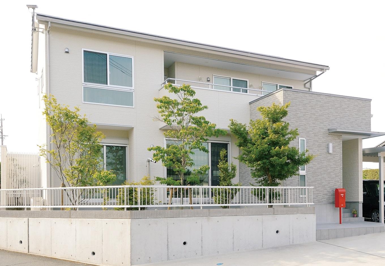 ハウジング小林【デザイン住宅、収納力、間取り】シンプルな白の外観に赤いポストがアクセント。バルコニーには屋根をかけてあるので、洗濯物を干したまま出かけても安心