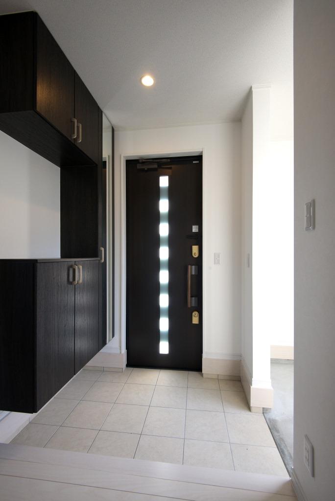 メテックス建築事務所【1000万円台、子育て、省エネ】ドアのガラス部分からは光が差し込み明るい玄関。その横には土間の収納も備えられている