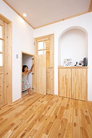 メテックス建築事務所【1000万円台、子育て、収納力】アーチがかわいいニッチは、下部を扉付きの収納に。雑貨を飾ったり、電話台としてもぴったりなスペース。地下収納の出入り口はここから