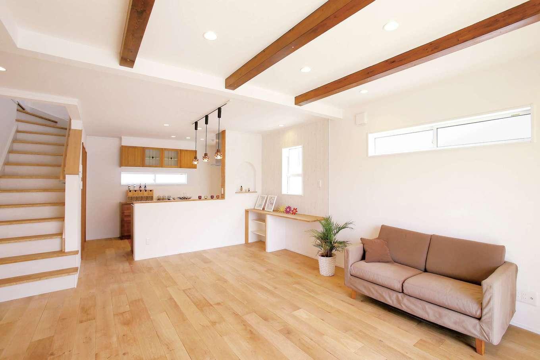 片桐建設【1000万円台、デザイン住宅、輸入住宅】リビングの天井の梁を現しにしたことで段差が生まれ、キッチンとの変化をつけた。無垢のフローリングは冬でも裸足で過ごせるほど暖かい