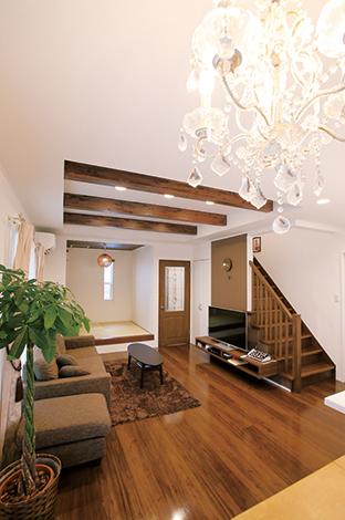 片桐建設【子育て、輸入住宅、間取り】キッチンから家族の様子が見渡せるリビングは、畳コーナーと合わせると20畳の大空間。ダークブラウンの床、白い壁、シャンデリアのトータルコーデが素敵