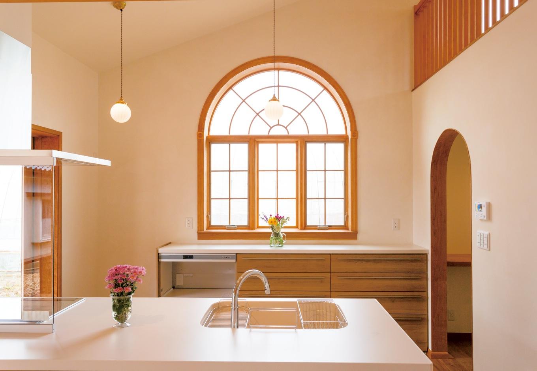 片桐建設【デザイン住宅、子育て、輸入住宅】奥さま一番のこだわりは、キッチン奥のアーチの木窓。経年変化が楽しみなチェリー材を使い、『片桐建設』が造作した。映画に登場するような外国の家を思わせる