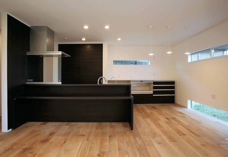片桐建設【デザイン住宅、輸入住宅、省エネ】LDKは、白と木の空間に、キッチンはブラックで統一し、壁の上と下に横長の窓を配した