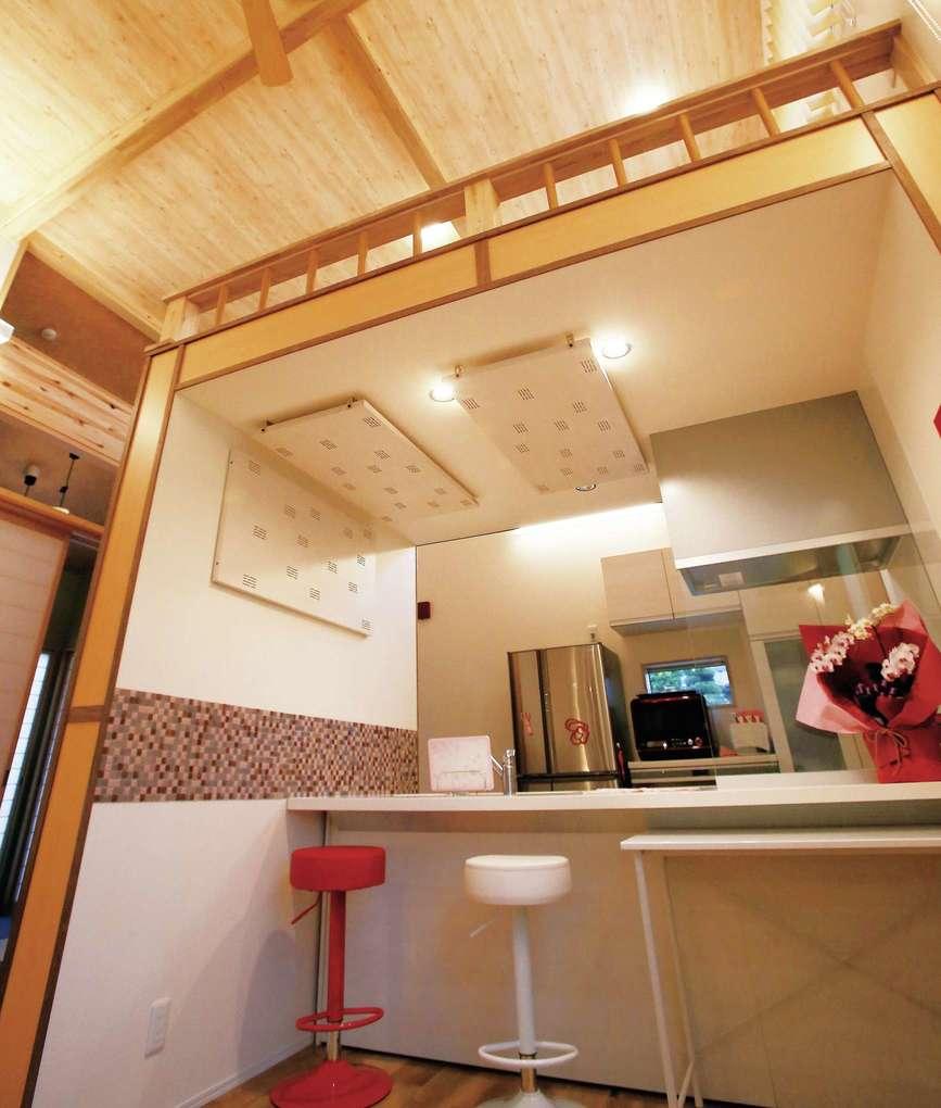 片桐建設【デザイン住宅、自然素材、夫婦で暮らす】キッチンのカウンターには色違いのスツールを設置。キッチン上にはロフトがあり、こちらもお孫さんの遊び場に