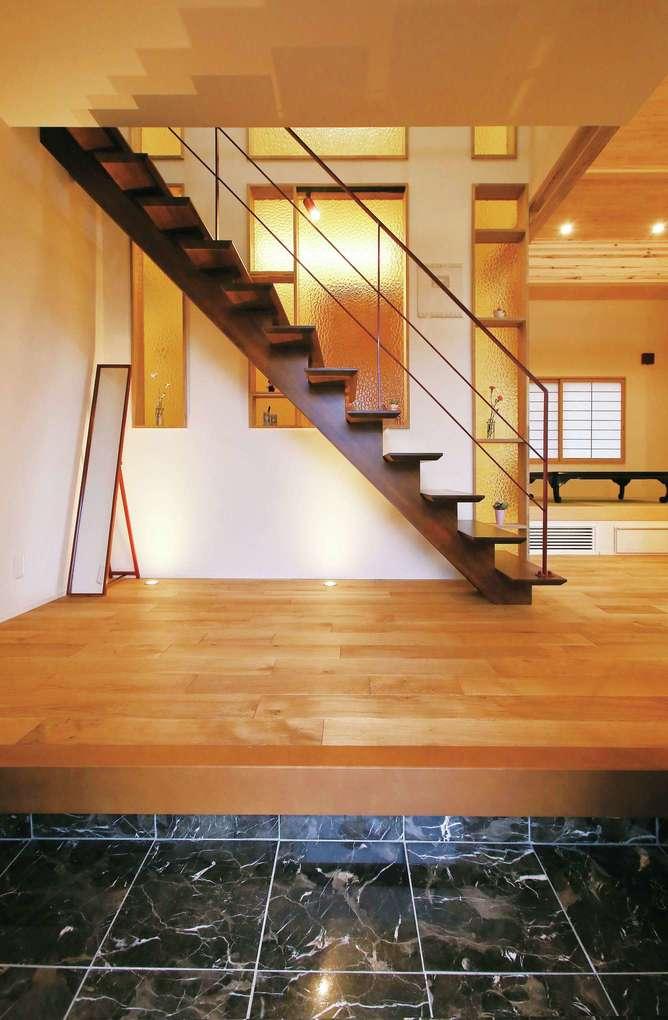 片桐建設【デザイン住宅、自然素材、夫婦で暮らす】玄関ホール。階段横の壁にはめ込んだイエローのガラスは、ご夫妻が独自にイタリアから取り寄せた