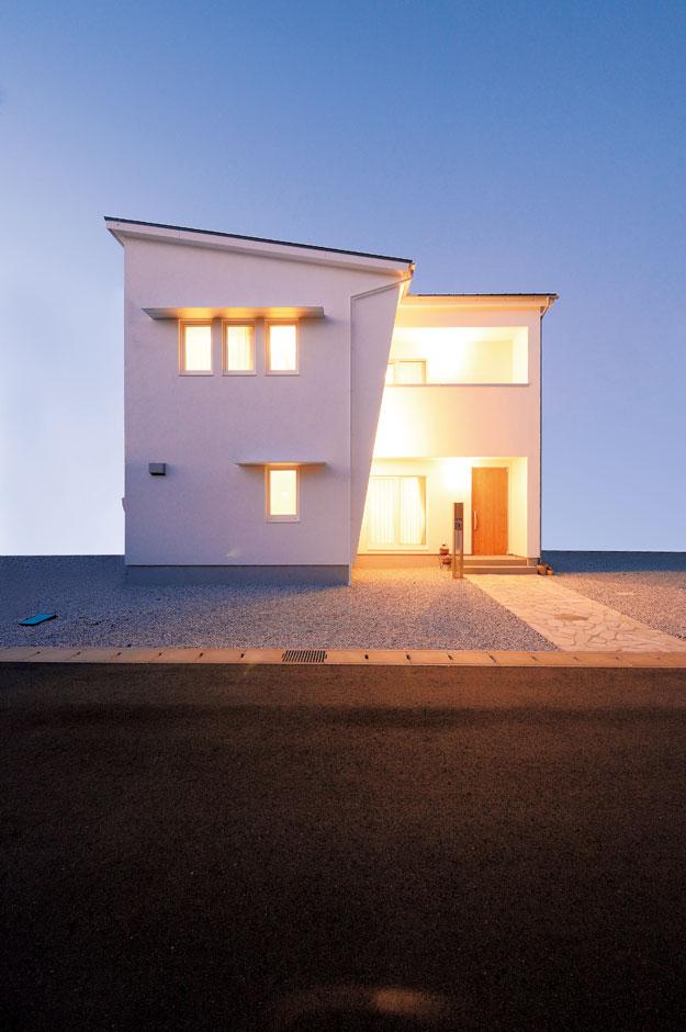 低燃費住宅 静岡(TK武田建築)【子育て、自然素材、省エネ】外壁はメンテナンスフリーなドイツ製の「アルセコ」。斜めの壁は内側に照明を取り付け、夜は違った表情を見せる。窓から入る直射日光を遮る長い庇にも注目