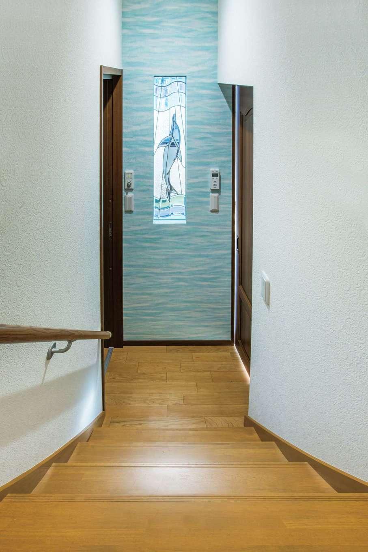 工藤建設【狭小住宅、省エネ、間取り】階段室とリビングの間仕切壁は、イルカのステンドガラスとブルーの壁紙で海をイメージ