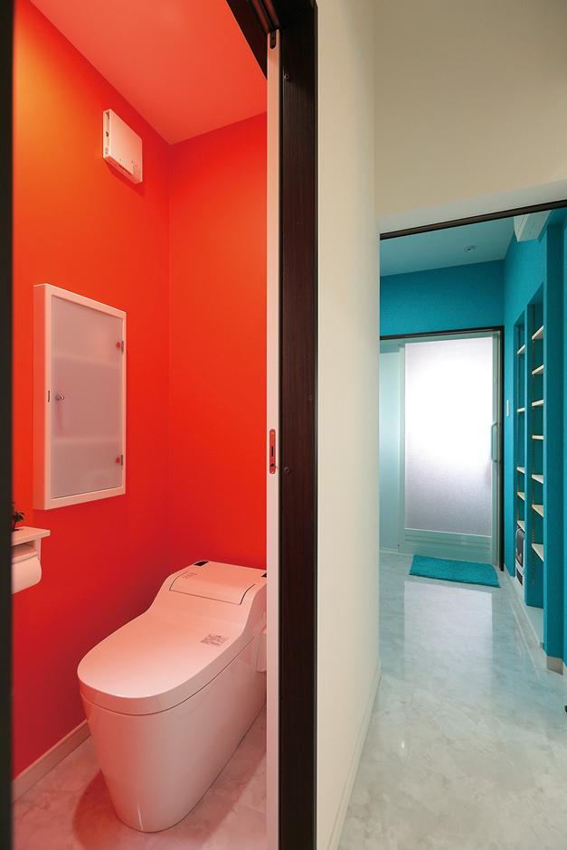 工藤建設【デザイン住宅、二世帯住宅、屋上バルコニー】トイレはエルメスオレンジ、洗面は川をイメージしたブルー。ドアを開けた瞬間ハッとする鮮烈な色合わせ