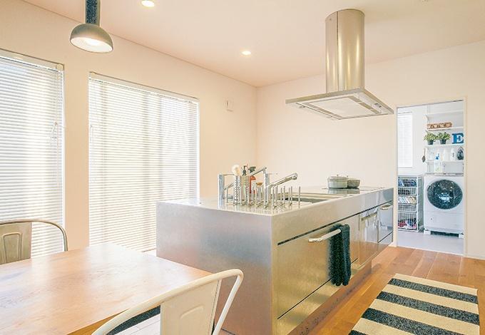 キッチンの下はビルトインタイプの食洗機と鍋などの収納スペース。手前にダイニングテーブル、奥にランドリールームが一直線に並び、家事動線もしっかり考えられている