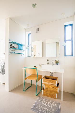 洗面は窓も鏡も照明も2つずつを左右対照に配置。ブルーを差し色に使って爽やかなイメージに仕上げた