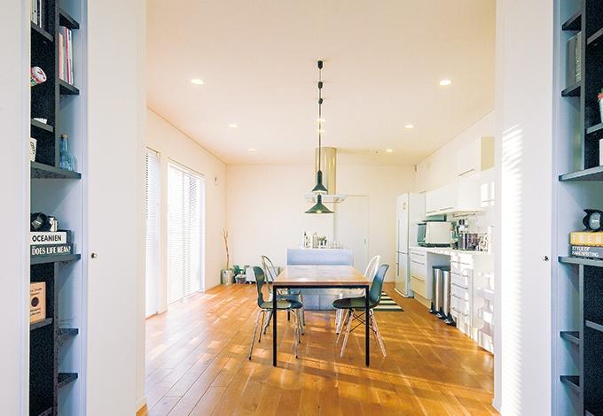 中庭を眺めながら料理ができる、アイランド型のステンレスキッチンがK邸の主役。ダイニングテーブルは床と同じナラ材で、足が黒いものをセレクト。 1つ1つ異なるスツールにもセンスの良さが光る。 手前の飾れるニッチ棚は『仲田工務店』が造作して黒く塗装したオリジナル