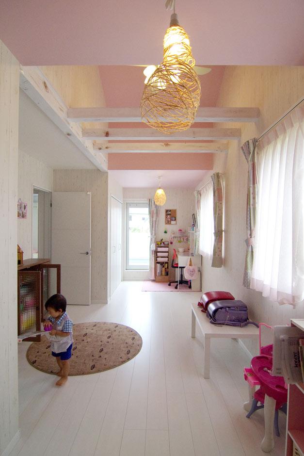 住起産業【子育て、収納力、和風】年齢も近い姉妹のお部屋。あえて空間を分けず、将来壁で仕切ることもできるように、ドア、クローゼット、窓、バルコニーへの出入りも同じように対である。屋根の形状に合わせて天井を高くし、梁を活かした空間に仕上がっている。梁はご主人がペイント。ピンク×ホワイトの空間が女の子の心をくすぐる