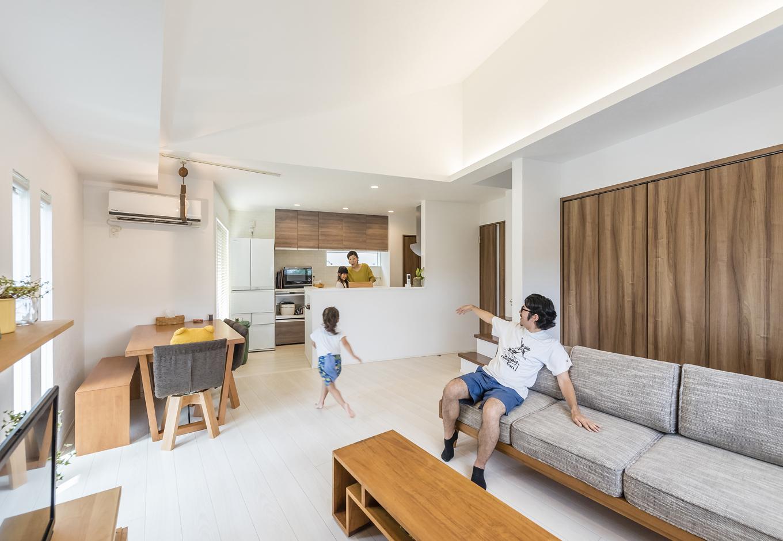 住起産業【二世帯住宅、狭小住宅、屋上バルコニー】リビング・ダイニングが見渡せるキッチンは、お子さんがお手伝いしやすいのもポイント。キッチンの横には小さなバルコニーがあり、プランターを置いて小さな家庭菜園も楽しめる。勾配天井や間接照明が、空間に広がりをもたらす