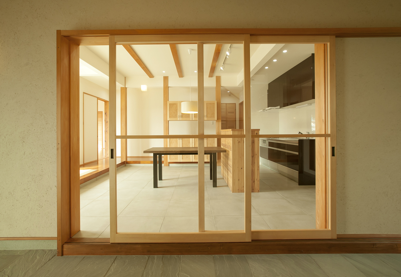 キッチンは玄関土間からつながり、大きなアクリルの建具を使用。夏場はフルオープンにできるため土間との一体の使い方ができる