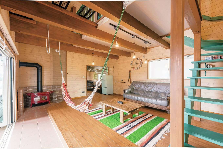 広いワンルームの室内。木の温もりに包まれたおおらかな空間にアンコールの薪ストーブが映える