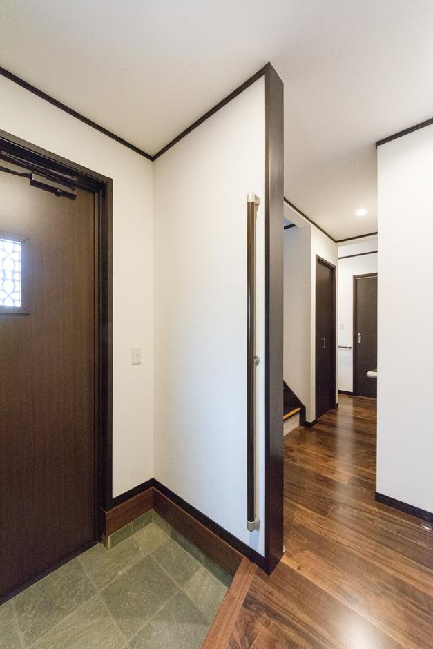 イーホーム【収納力、二世帯住宅、屋上バルコニー】石畳とウォールナットの床が落ち着いた雰囲気を醸し出している玄関。長めに設置した昇降用の手すりはお子さんからご年配まで安全に使用できる