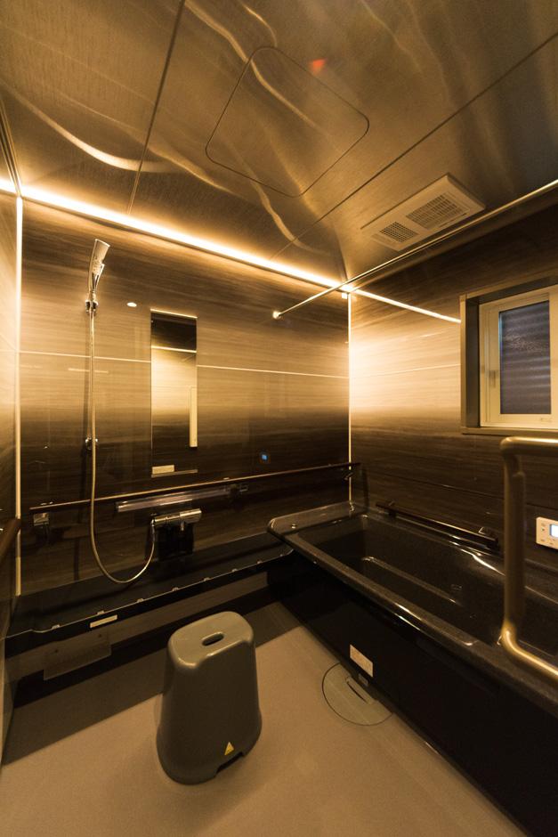イーホーム【収納力、二世帯住宅、屋上バルコニー】ステンレス天井とLEDのライン照明を付けた浴室。浴槽まで手すりに沿って歩ける配慮も