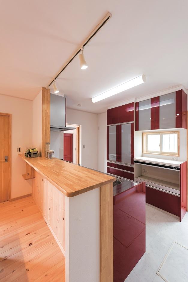 イーホーム【子育て、収納力、間取り】脇のドアを開けると玄関に直結。そしてリビングへと回遊できる、赤のアクセントが効いたキッチン。パネルの色と土間収納の扉の色をコーディネートしているので、雑多な印象がない
