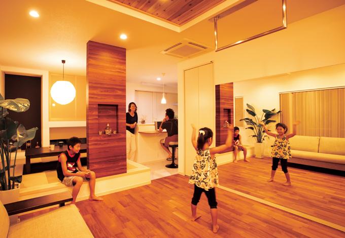スズイチ【デザイン住宅、子育て、間取り】リビングとダイニングキッチンを緩やかに ゾーニングした心地いい空間。大型の鏡の 前で長女がダンスレッスンに励む。木目調の 意匠柱の裏はカレンダーが貼ってあり、家族 みんながスケジュールを確認できる