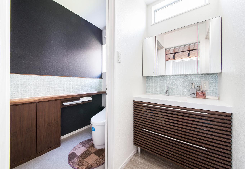 内田建設【デザイン住宅、狭小住宅、間取り】洗面室とトイレにあしらったガラスタイルが爽やかな水回り。トイレの収納はネットで見つけたお気に入りを大工さんにアレンジしてもらい設置。ラメ入りの黒いクロスがおしゃれ