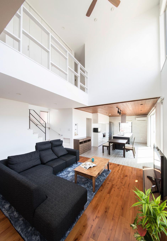 内田建設【デザイン住宅、狭小住宅、間取り】木をアクセントにした上質感あふれるLDK。白を基調とした空間に南面の窓から降り注ぐ光が反射する、明るく開放的な空間。リビングの床材は、建材市で見つけた無垢のカバ材をチーク風に塗装することで、コストを抑えつつ高級感を出すことに成功した