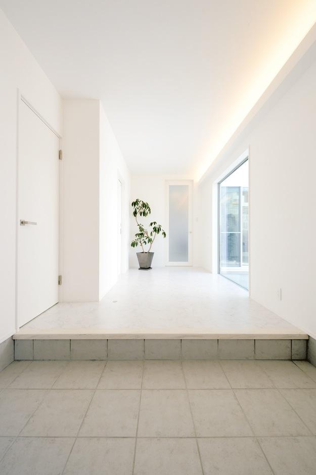 内田建設【収納力、建築家、ガレージ】中庭を望む窓から差し込む光が、ゆったりとした玄関ホールを照らす。すぐ横には土間続きのシューズクローゼットも