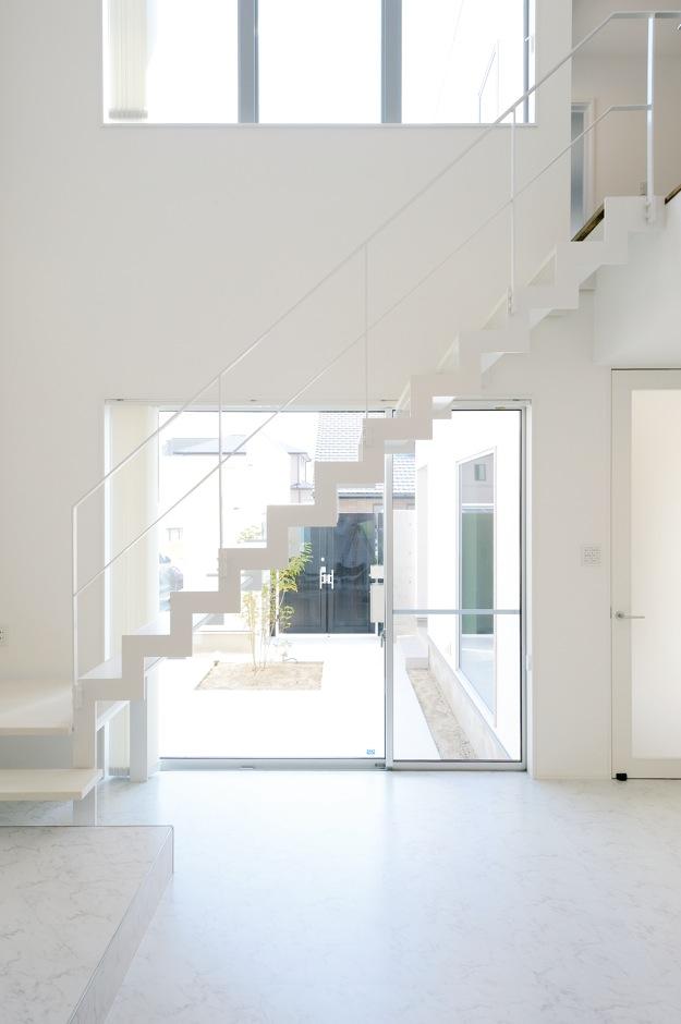 内田建設【収納力、建築家、ガレージ】純白のリビング階段が空間のアクセントに。鉄骨をベースに、踏み板には木を使用した。形状からイナズマ階段とも言う、蹴込み板がなく、骨組みだけのスタイリッシュなシルエット。リビングからはもちろん、中庭やガレージ、玄関ホールからも見えるように、あえて窓際にレイアウト。ソファに寝転がって、階段越しに見る空の景色がお気に入りなのだそう