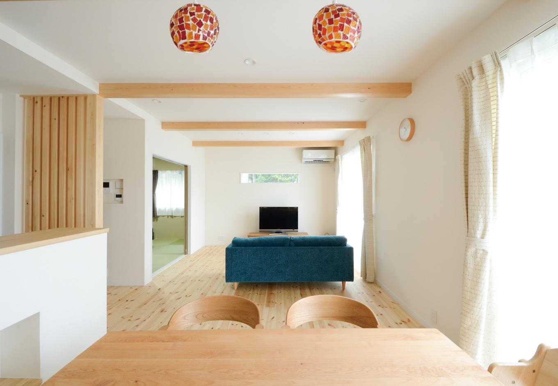 内田建設【収納力、間取り、建築家】20畳のLDK。南面の大きな開口部を開けると、ウッドデッキを介して庭とつながる。TVの上のスリット窓からも緑の借景を楽しめる