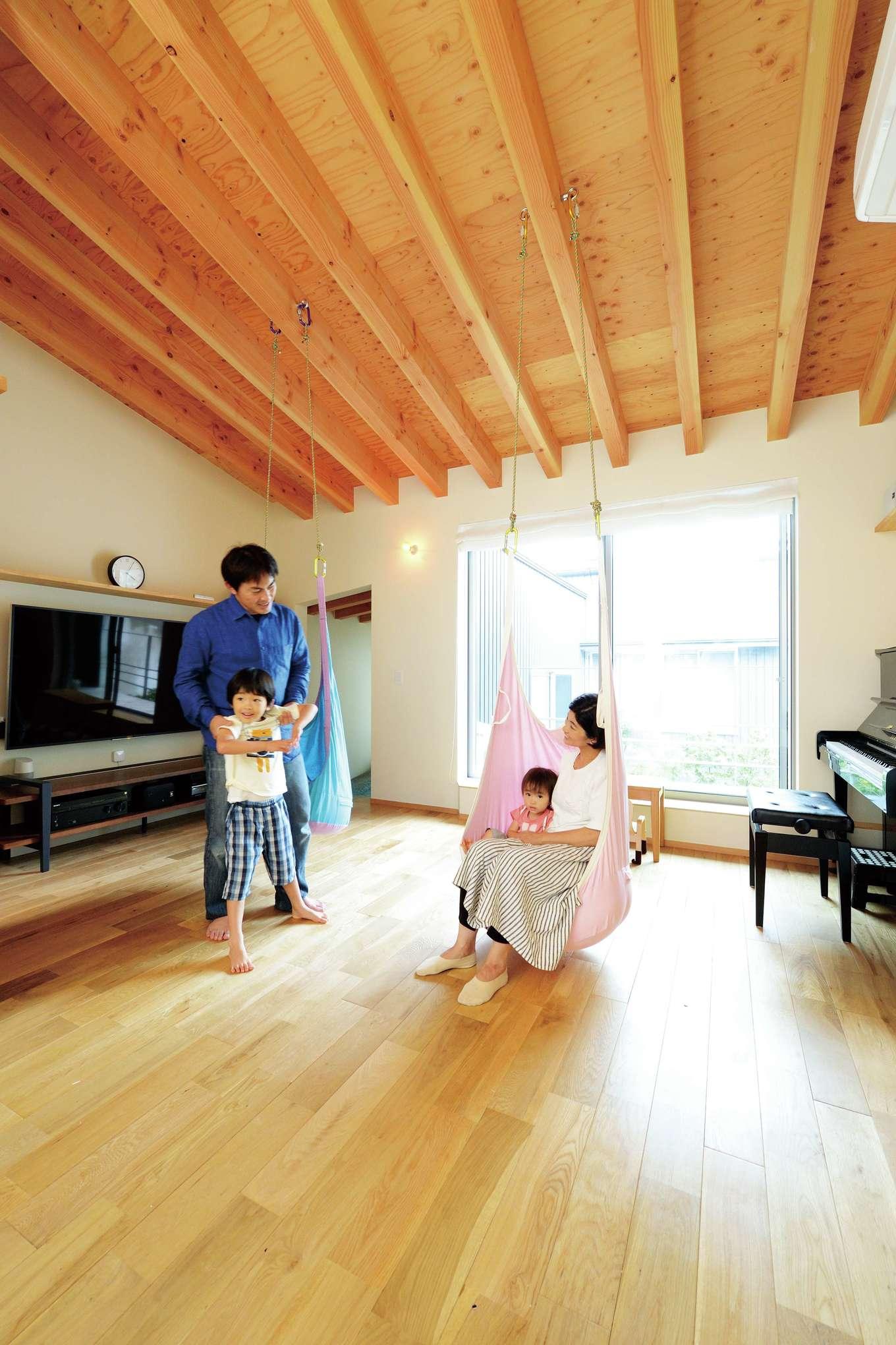 床にも天井にも無垢材を使用した子世帯のLDK。配線を隠せるTVボードを造作し、空間をすっきりと見せる。中庭の景色もリビングの一部として楽しめる