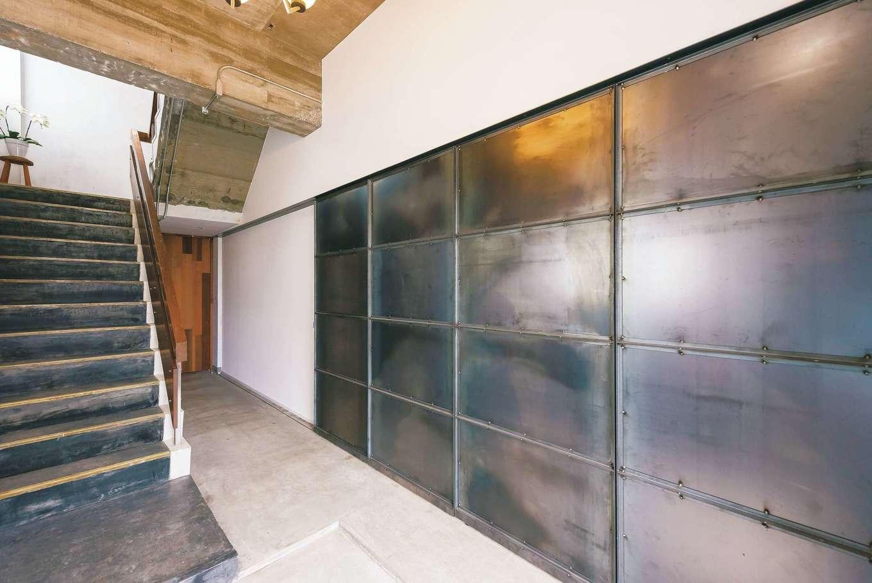 建杜 KENT(大栄工業)|2階ホール。鉄板を4枚組み合わせて加工し、土間の入口となる引き戸に仕上げた